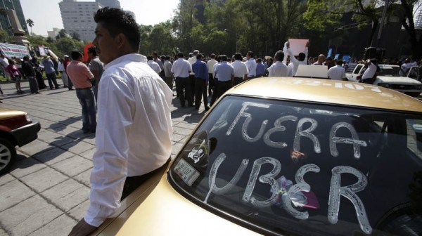 A local taxi driver leans on his car, with the words reading 'Uber out' written on the back windshield of his vehicle, during a protest in Mexico City, May 25, 2015. Uber said customers in Mexico City could use its service for free on Monday as local taxi drivers staged citywide protests against possible regulation of ride-hailing services such as the company's and Cabify. Local taxi drivers are holding the latest in a series of marches and road blocks across the city on Monday in protest against the possible legitimatizing of what they say are illegal services. REUTERS/Adan Gutierrez - RTX1EIJT