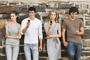 Full length portrait of young men and women holding cellphone