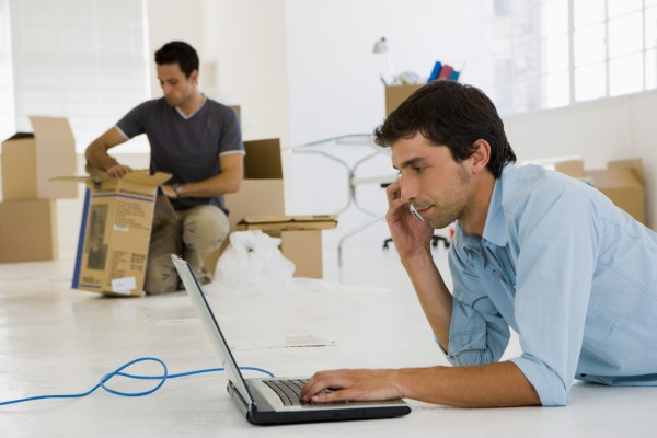 Man on cell phone with laptop in office space